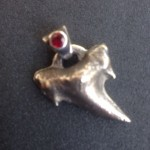 Fossilised Shark Tooth .. sand cast in silver with a synthetic, man made, Lab-grown Ruby set in the bale